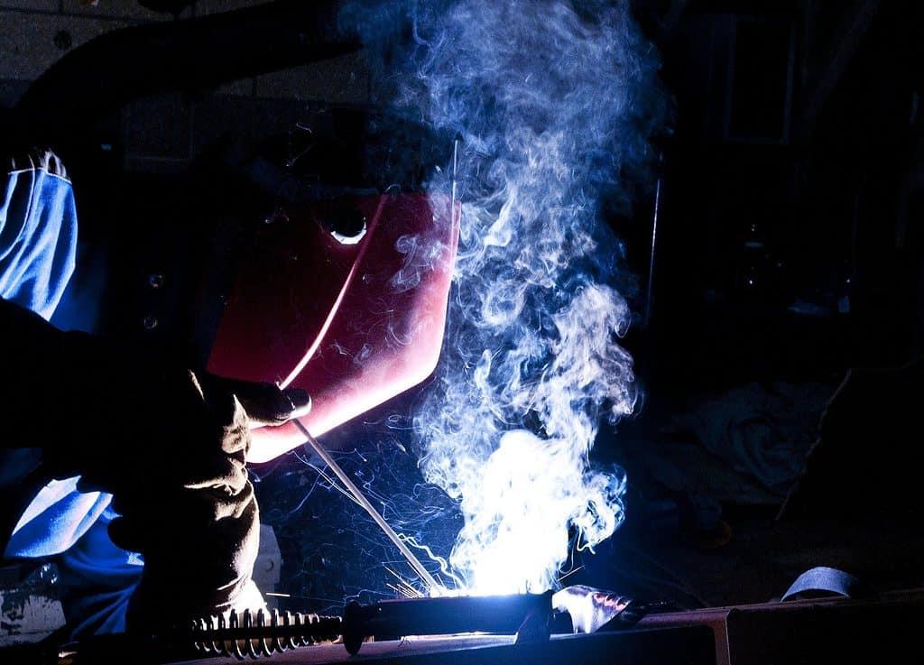 A welder uses an auto-darkening helmet as part of his regular PPE.